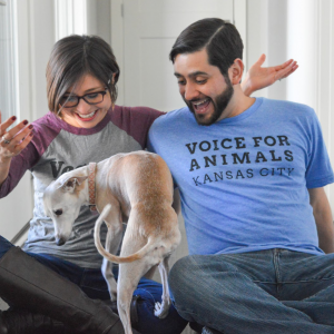 "Two models are climbed on by a cute dog and they seem surprised about it. One of them wears a handsome blue tee shirt with the words ""Voice for Animals Kansas City"" printed on it."