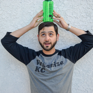 "Model stands holding a green bottle on his head wearing a gray baseball tee with black sleeves and the words ""veganize kc"" printed on the front in black ink"