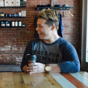 "Cool guy sits in a rustic coffee shop in a stylish gray baseball tee with blue sleeves and the words ""Voice for Animals Kansas City"" printed on it."