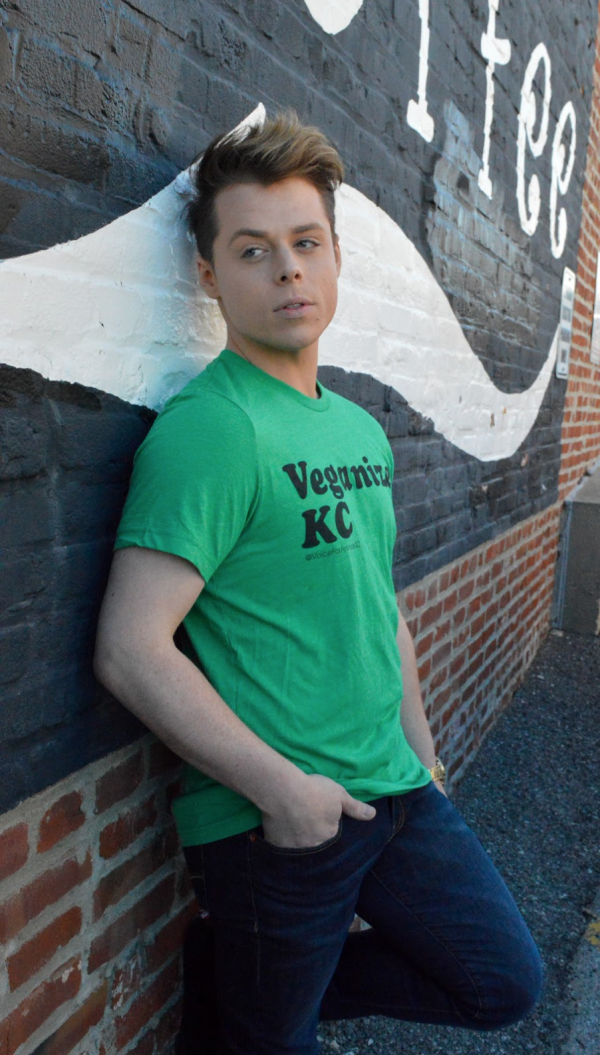 "Model leans casually against a brick wall while wearing a stylish green T-shirt with the words ""Veganize KC"" printed on the front in black ink"
