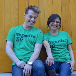 "Two models sit smiling side by side each wearing a green t-shirt with the words ""Veganize KC"" printed on them in black ink"