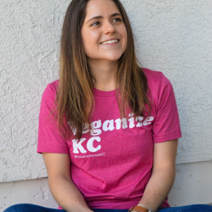 "Model sits smiling on the ground in a stylish pink T-shirt with the words ""Veganize KC"" printed on it in white ink."
